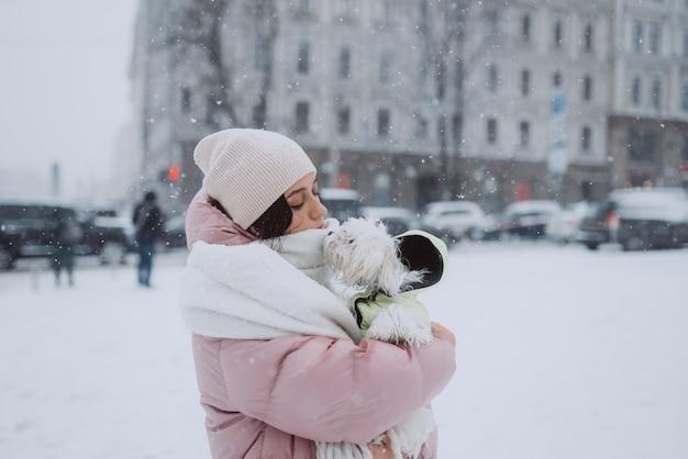 Menina com um cachorro nos braços a neve está caindo