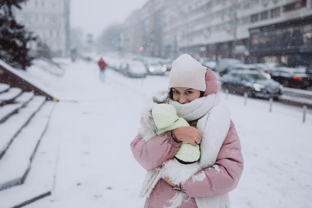 Menina com um cachorro nos braços a neve está caindo Foto gratuita