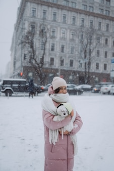 Menina com um cachorro nos braços em uma rua da cidade com neve caindo