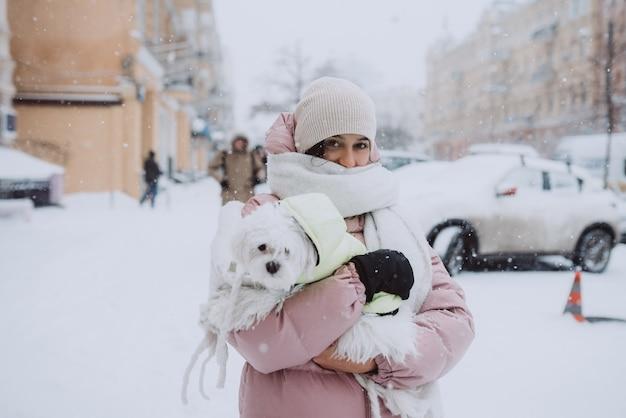 Menina com um cachorro nos braços enquanto a neve está caindo