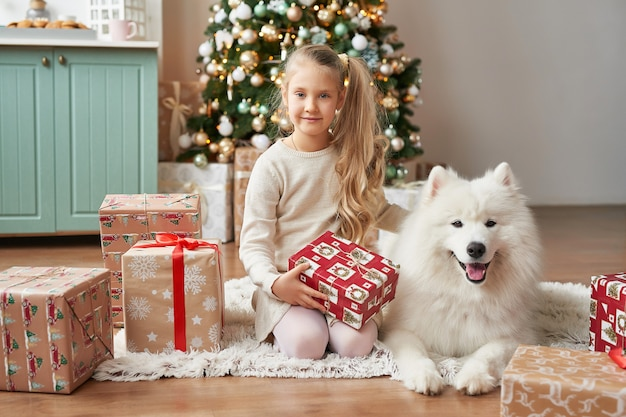 Menina com um cachorro perto da árvore de natal na cena do natal