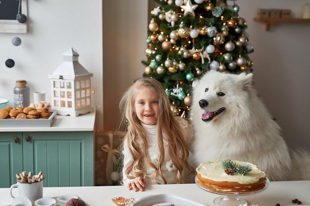 Menina com um cachorro perto da árvore de natal no fundo de natal