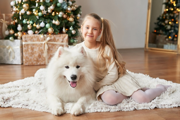 Menina com um cachorro perto da árvore de natal