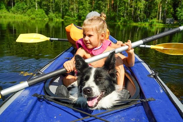 Menina com um cachorro sentado em um caiaque no lago.