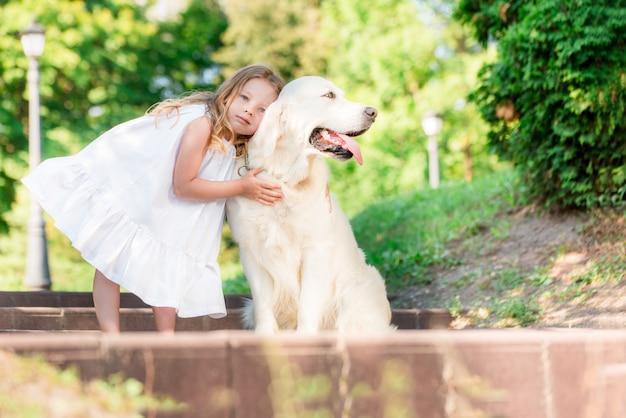 Menina com um cão branco grande no parque. uma menina de 5 anos linda no vestido branco abraça seu cachorro favorito durante uma caminhada de verão.