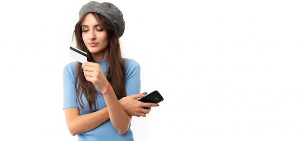Menina com um cartão de crédito com maquete e um telefone em um estúdio branco