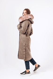 Menina com um casaco de inverno com gola de pele em um fundo branco