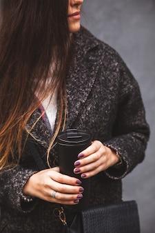 Menina com um casaco elegante com uma mão de manicure linda segurando um copo de vácuo preto em uma parede cinza