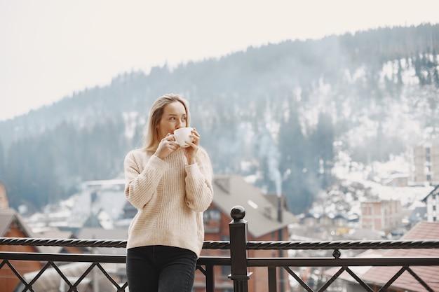 Menina com um casaco leve e quente. férias nas montanhas. senhora de cabelo comprido.