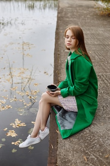 Menina com um casaco verde caminha ao longo do outono do lago
