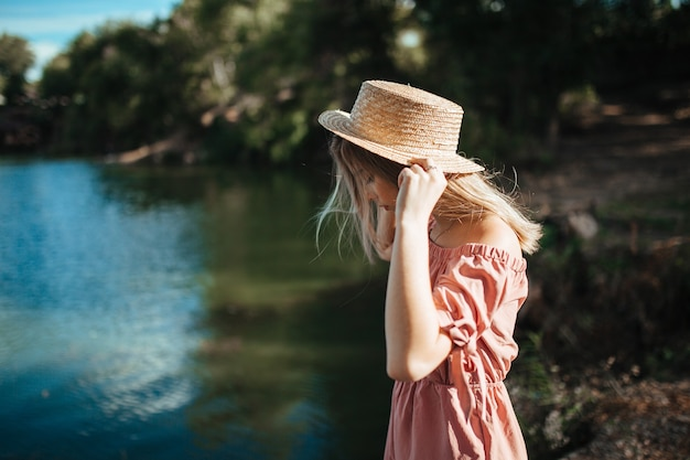 Menina com um chapéu de aldeia na margem do rio