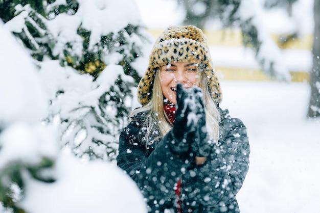 Menina com um chapéu de inverno elegante com uma estampa de leopardo se alegra na neve