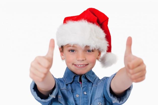 Menina com um chapéu de natal e os polegares para cima
