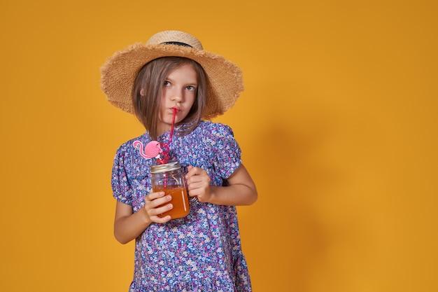 Menina com um chapéu de palha e óculos de sol está sorrindo em uma menina de criança de fundo amarelo em um dre azul.
