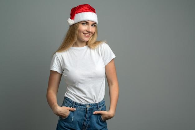 Menina com um chapéu de papai noel vermelho isolado em cinza