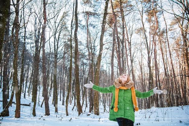 Menina com um chapéu de parque luvas fofas em pé com os braços estendidos na floresta de neve de inverno