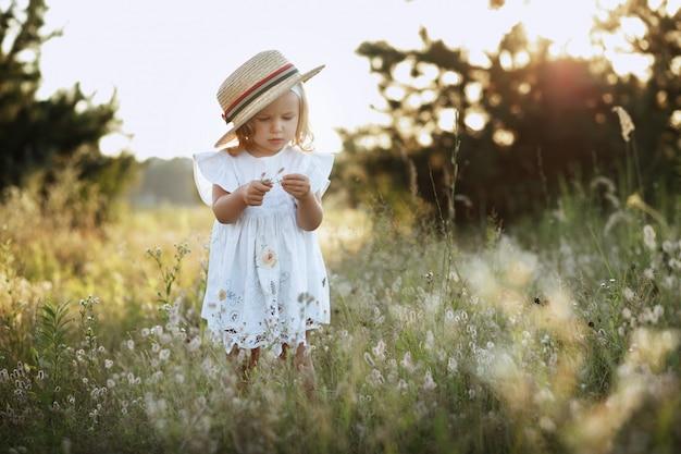 Menina com um chapéu de verão na caminhada ao pôr do sol