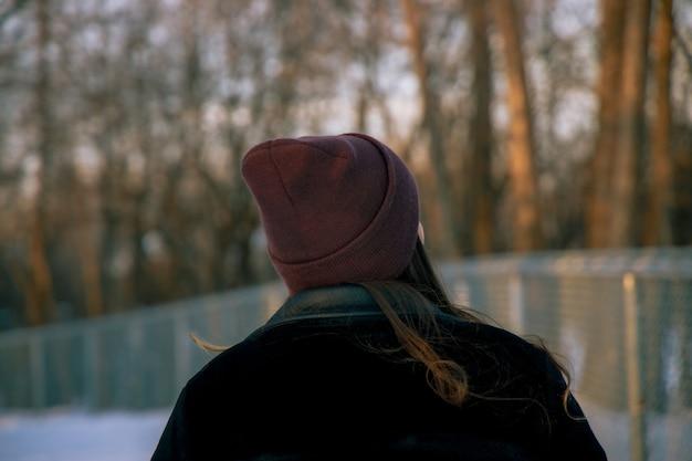 Menina com um chapéu parada na floresta durante o dia