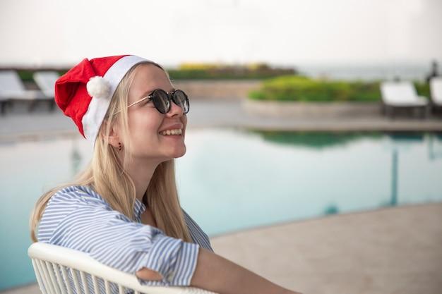 Menina com um chapéu vermelho de natal ao lado da piscina.