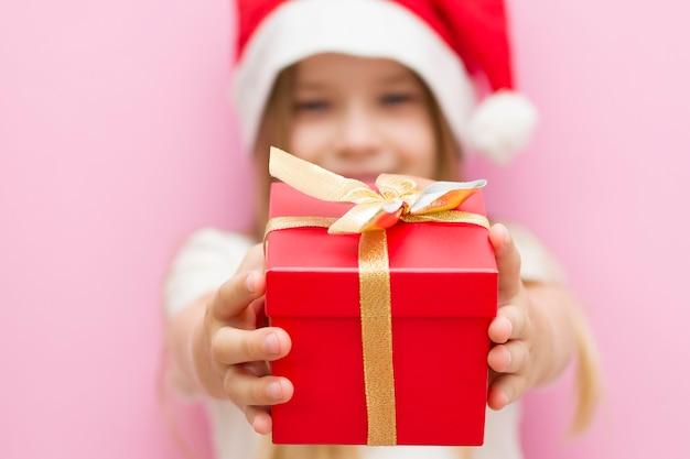 Menina com um chapéu vermelho de natal apresenta uma caixa vermelha com um laço de ouro, um presente. sorri. o novo ano é 2021. close up