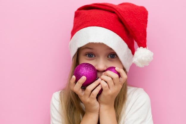 Menina com um chapéu vermelho de natal tem balões rosa de natal nas mãos. fechar-se. feliz ano novo 2021