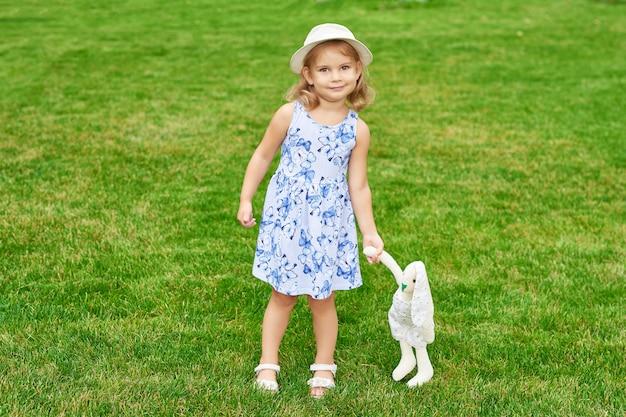 Menina com um coelho no parque