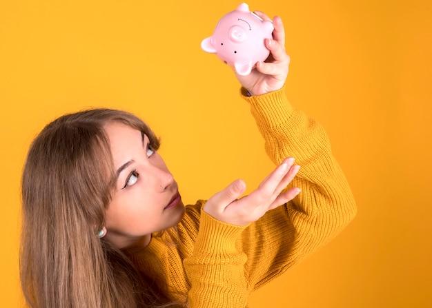 Menina com um cofrinho, não tem dinheiro está olhando para o cofrinho vazio