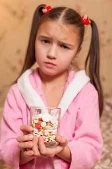 Menina com um copo cheio de comprimidos