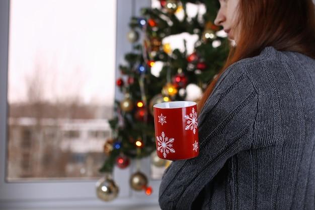 Menina com um copo de bebida quente parada em frente a uma janela na véspera de ano novo