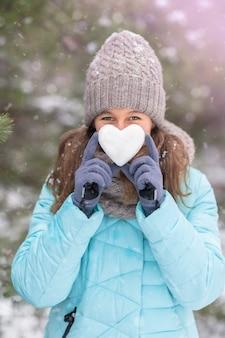 Menina com um coração de neve nas mãos na natureza