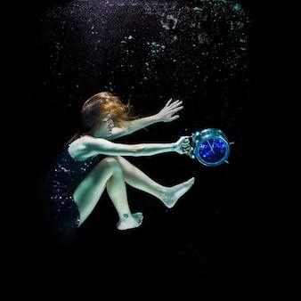 Menina com um despertador sob a água