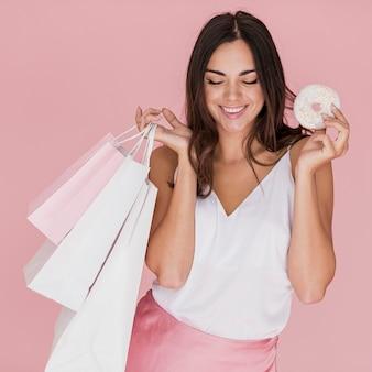 Menina com um donut e sacolas de compras em fundo rosa