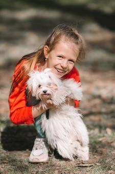 Menina com um filhote de cachorro branco, um filhote de cachorro nas mãos de uma menina