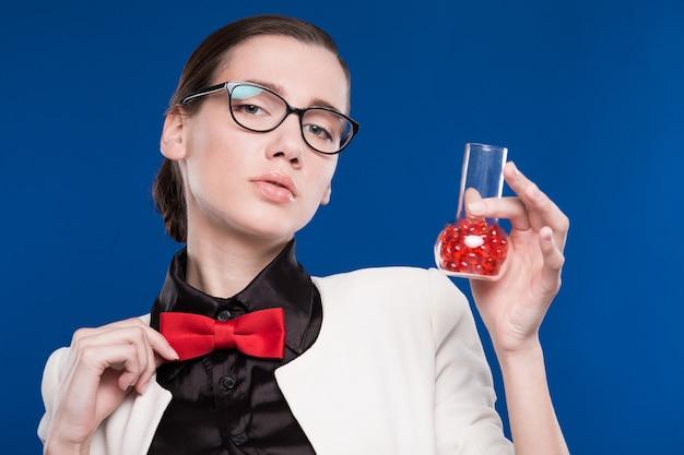 Menina com um frasco na mão e uma borboleta vermelha no pescoço