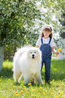 Menina com um grande cão branco no parque.