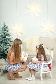 Menina com um grande presente de natal, juntamente com a mãe posa perto da árvore de natal.