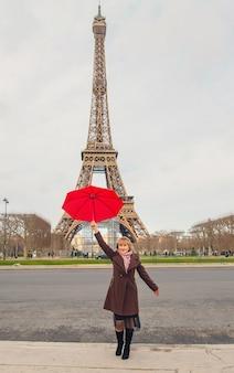 Menina com um guarda-chuva vermelho perto da torre eiffel em paris. foco seletivo.