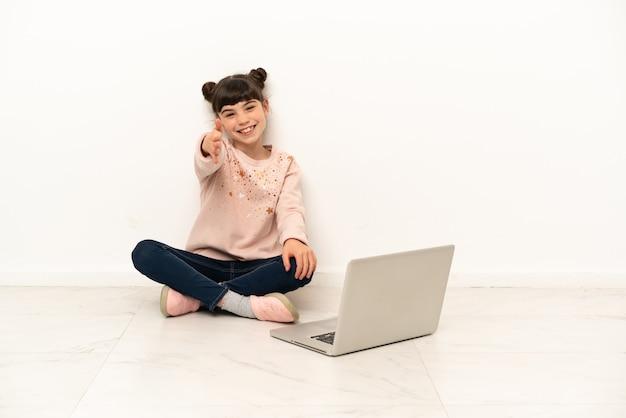 Menina com um laptop sentada no chão apertando as mãos para fechar um bom negócio