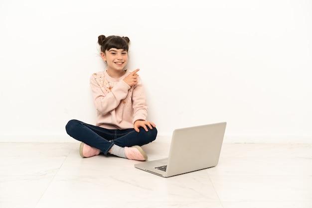 Menina com um laptop sentada no chão apontando para o lado para apresentar um produto