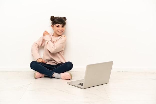 Menina com um laptop sentada no chão comemorando uma vitória