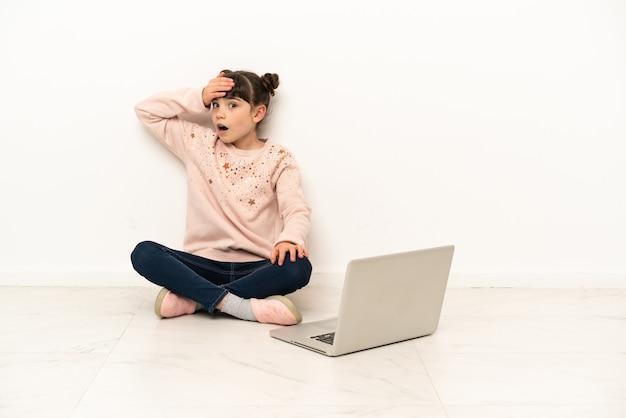 Menina com um laptop sentada no chão fazendo gesto de surpresa enquanto olha para o lado