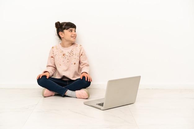 Menina com um laptop sentada no chão, olhando para o lado e sorrindo