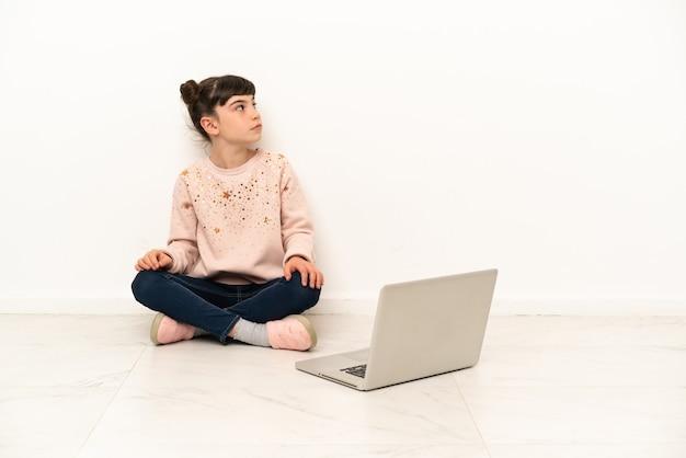 Menina com um laptop sentada no chão olhando para o lado