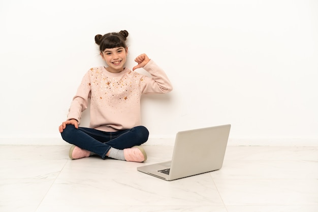 Menina com um laptop sentada no chão orgulhosa e satisfeita