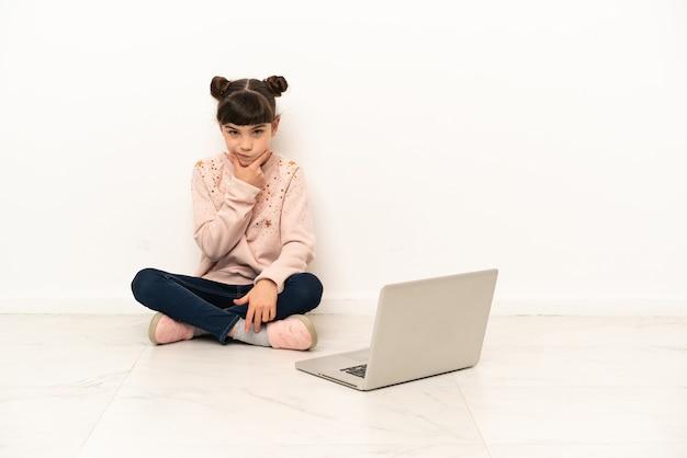 Menina com um laptop sentada no chão pensando
