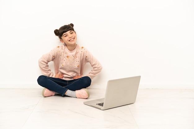 Menina com um laptop sentada no chão, posando com os braços na cintura e sorrindo