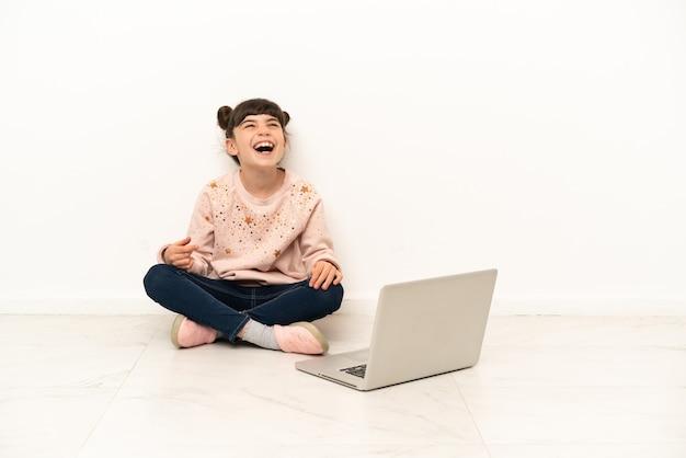 Menina com um laptop sentada no chão rindo