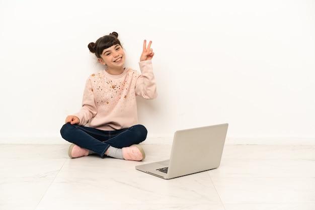 Menina com um laptop sentada no chão sorrindo e mostrando sinal de vitória