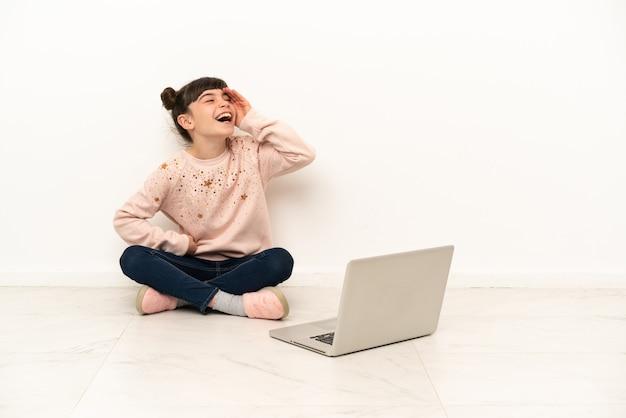 Menina com um laptop sentada no chão sorrindo muito