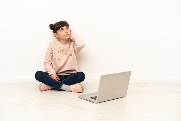 Menina com um laptop sentada no chão, tendo dúvidas